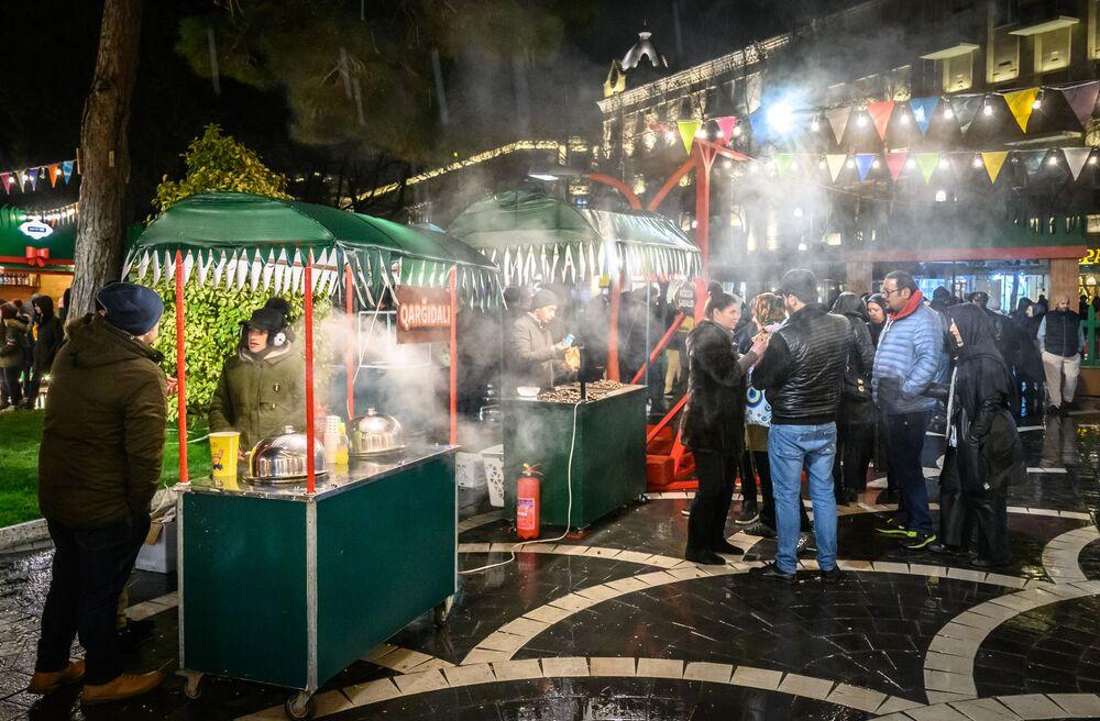 Lidé kupují tradiční sladkosti během Nourúzu na svátečném trhu v Baku, Ázerbájdžán.