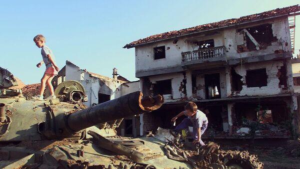 Děti si hrají na zničeném tanku, který byl zničen během bombardování NATO - Sputnik Česká republika