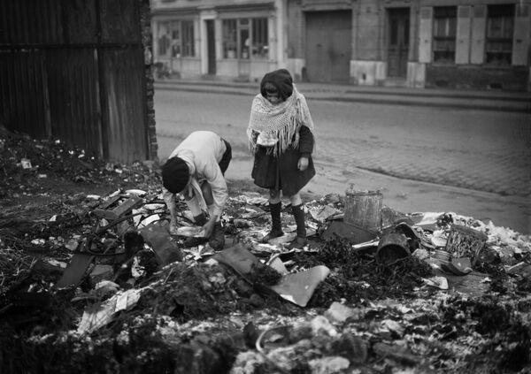 Dvě děti hrabající se v odpadcích na jedné pařížské ulici během druhé světové války, leden 1945 - Sputnik Česká republika