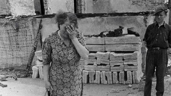 Žena plačící nad popelem lidí spálených v peci, německý koncentrační tábor Majdanek, Polsko - Sputnik Česká republika