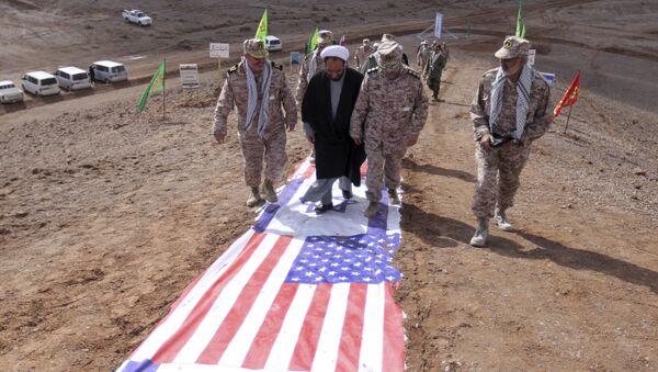 Členové Íránských revolučních gard šlapou po vlajkách Izraele a USA - Sputnik Česká republika