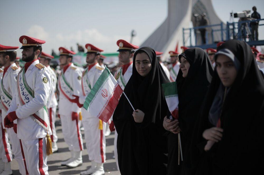 Islámské revoluční gardy ve formálních oděvech a demonstranti během oslavy 33. výročí islámské revoluce na náměstí Svobody v Teheránu