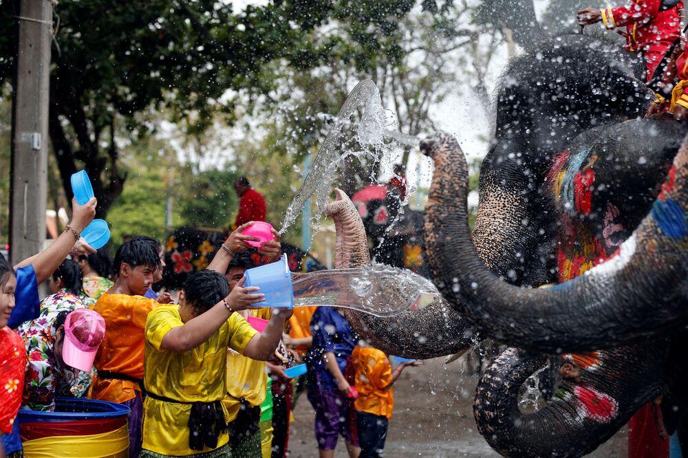 Lidé a sloni se polévají vodou během oslav nového thajského roku