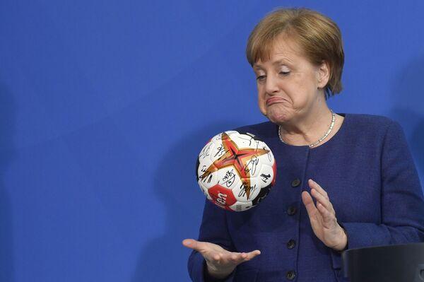 Německá kancléřka Angela Merkelová s míčem na házenou - Sputnik Česká republika