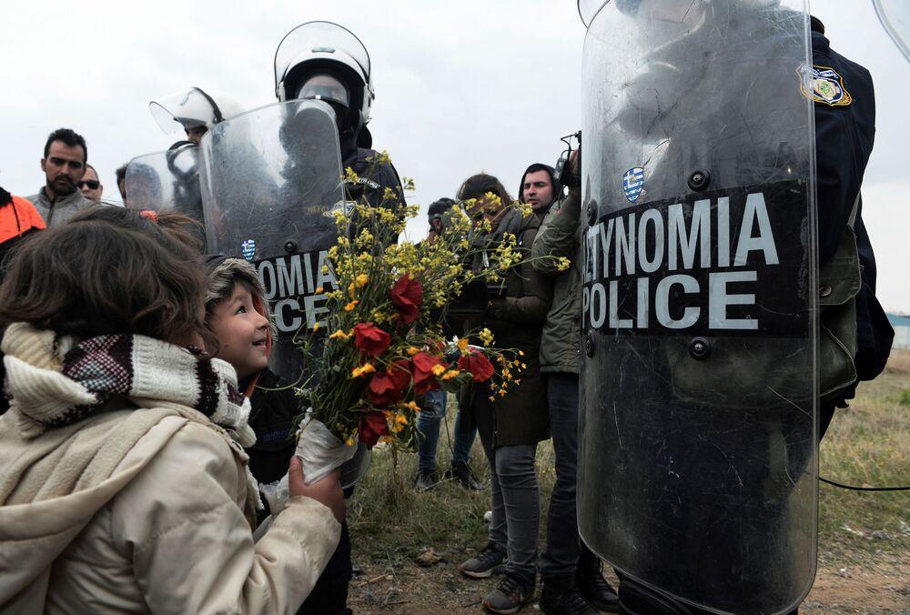 Děti dávají květiny řeckým policistům po střetech v uprchlickém táboře v Diavatu, Řecko