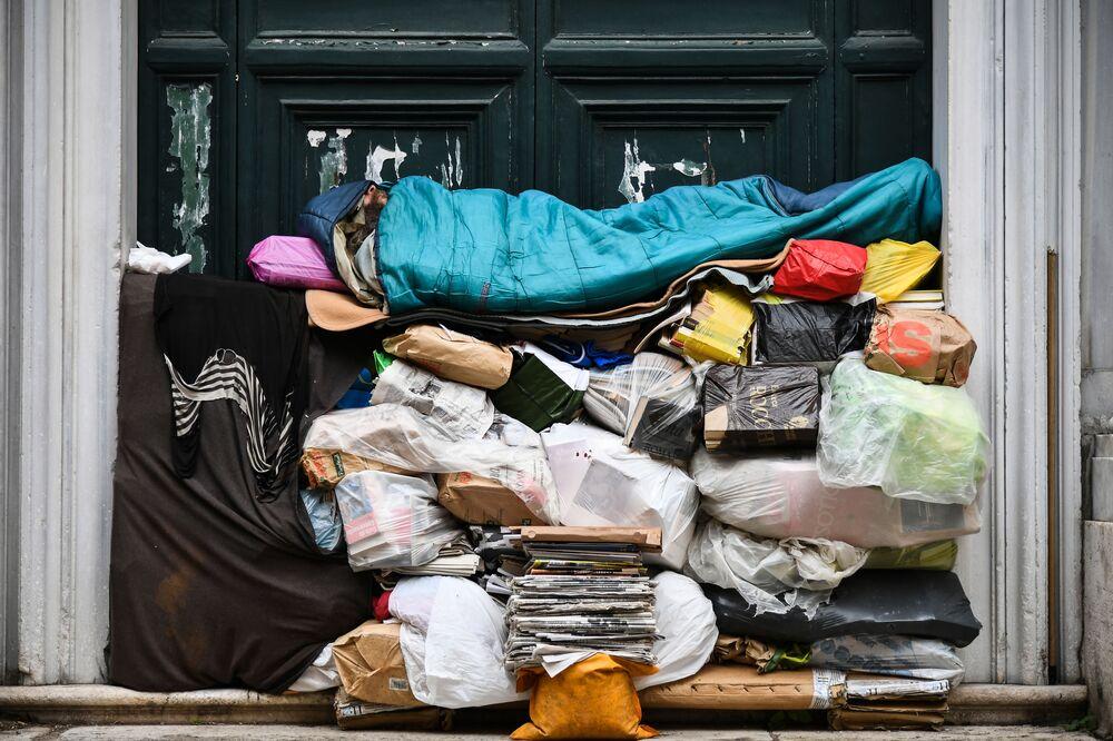 Bezdomovec spí na hromadě odpadků pod verandou v Římě, Itálie