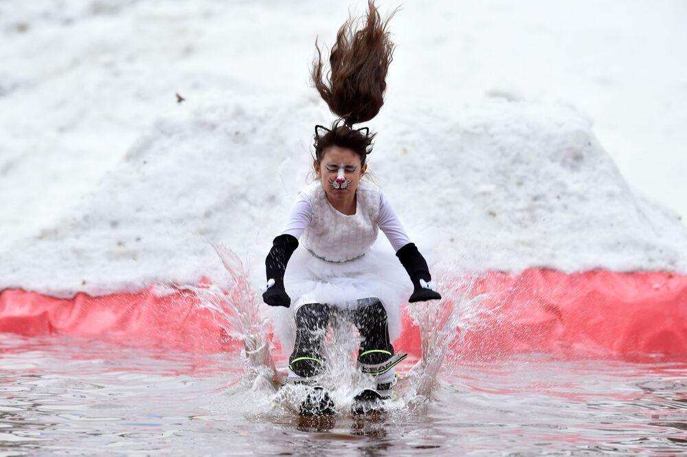 Účastníce humoristické soutěže Californication 9.0 věnované ukončení zimní sezóny lyžuje v bazénu nedaleko města Logojsk, Bělorusko