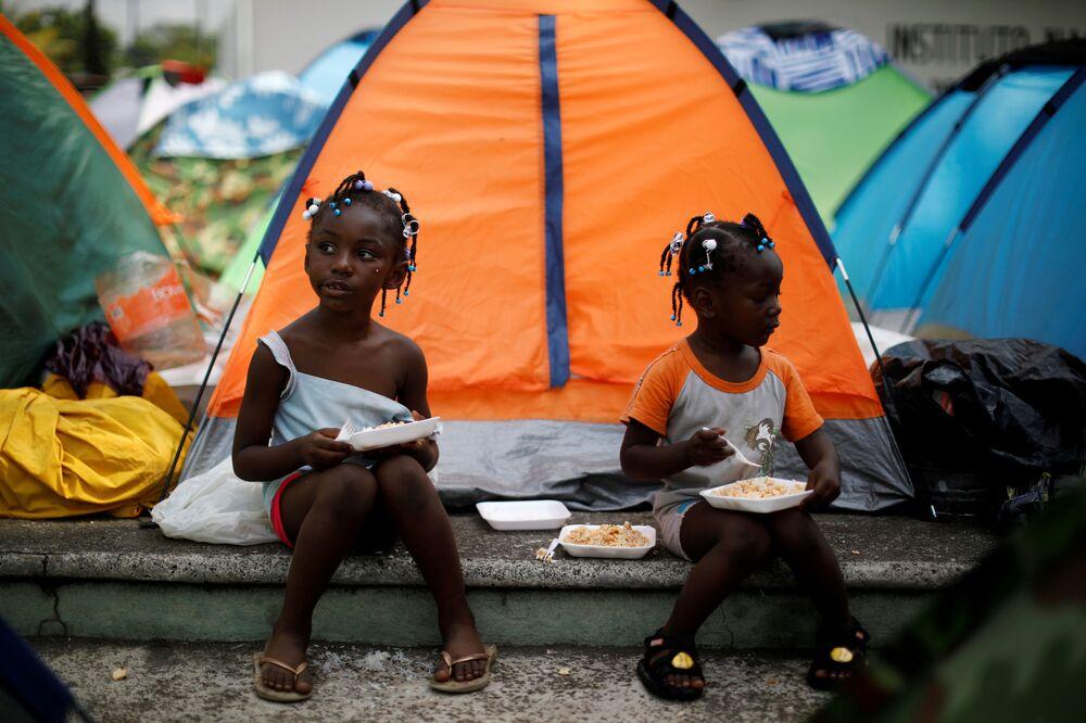 Dívky z Konga jedí poblíž svého stanu v improvizovaném táboře vedle Národního institutu pro migraci (INM) v mexickém Tapačule
