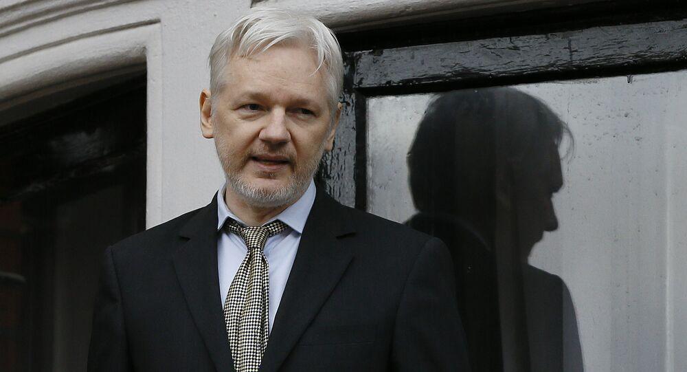 Julian Assange zadržený britskou policií. Archivní foto.