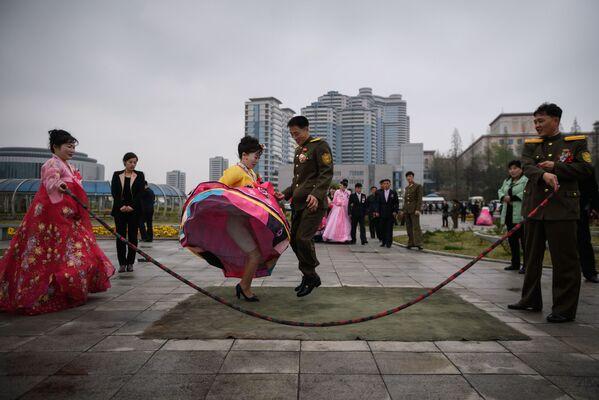 Nevěsta a ženich skáčou přes švihadlo během focení v parku v Pchjongjangu, Severní Korea - Sputnik Česká republika