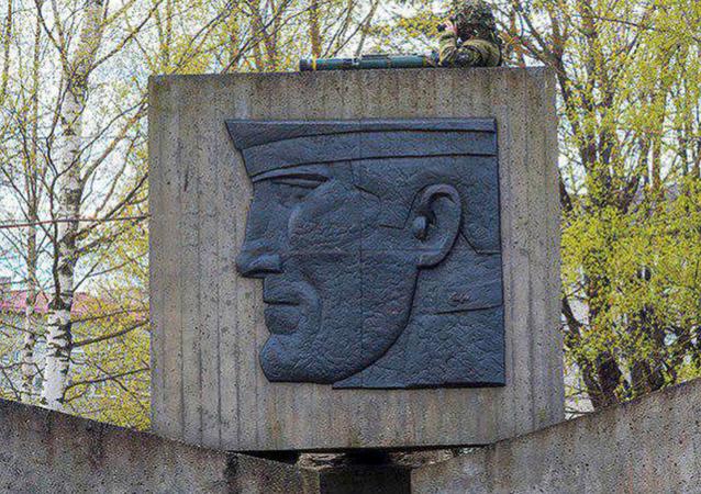 Voják NATO v Estonsku se zbraní vylezl na pomník sovětským vojákům