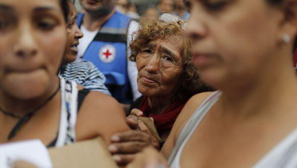Obyvatelé v řadě pro prázdné kontejnery a tablety na čištění vody během akce Červeného kříže v Caracasu - Sputnik Česká republika