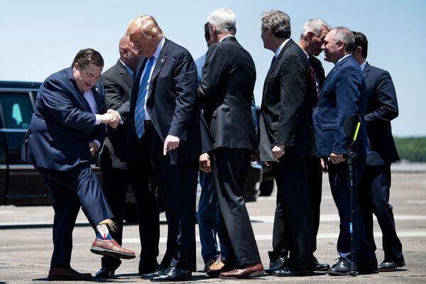 Víceguvernér státu Louisiana, Billy Nungesser, na letišti ukazuje americkému prezidentovi Donaldovi Trumpovi své ponožky s jeho podobiznou. - Sputnik Česká republika